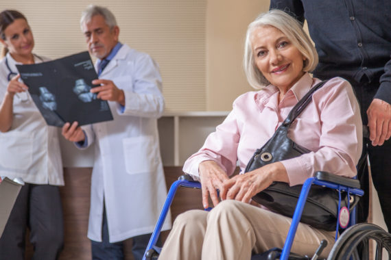 Happy woman in 60s on the wheelchair assisted at the hospital. Health concept.
