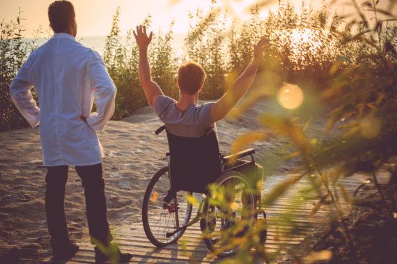A man on wheelchair and his nurse enjoying sunrise on a beach.